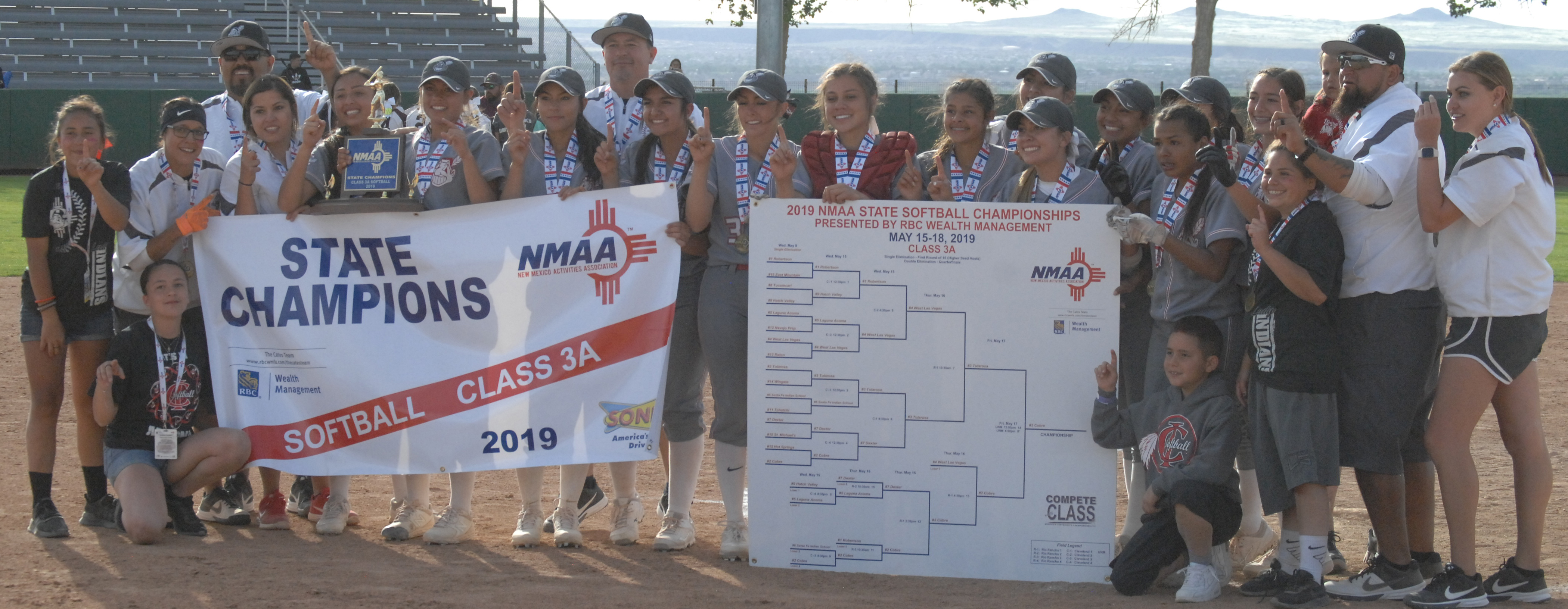 "The Cobre High School Lady Indians pose with the championship trophy and banner after beating Tularosa 12-11 in the ""if"" game of the state Class AAA championship round Friday afternoon at the University of New Mexico softball field in Albuquerque."