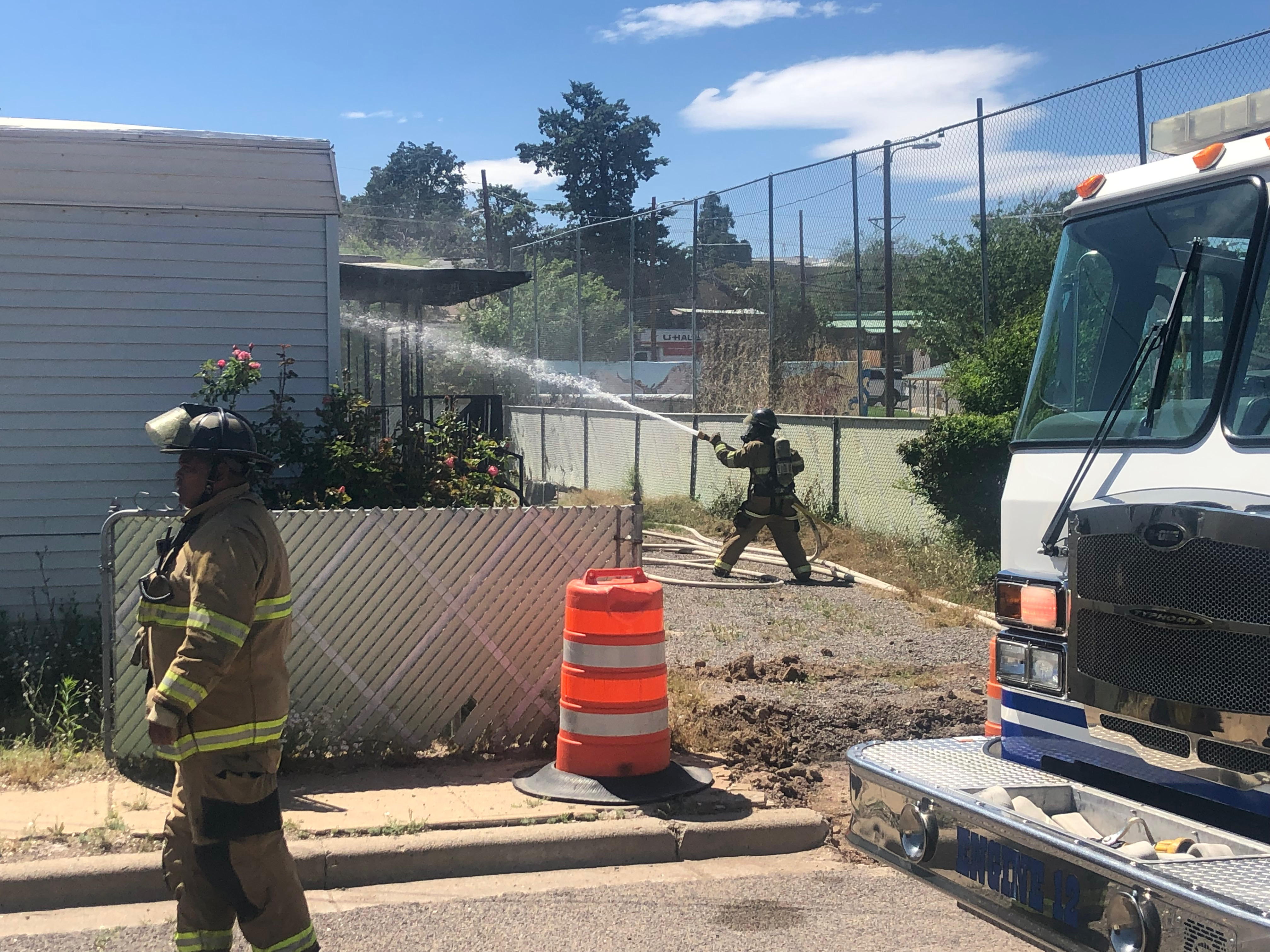 (Press Staff Photo)  A Silver City Fire Department firefighter sprays water onto a home on Arizona St. on Thursday afternoon. The fire started on the front porch and made its way inside, burning the kitchen and living room.