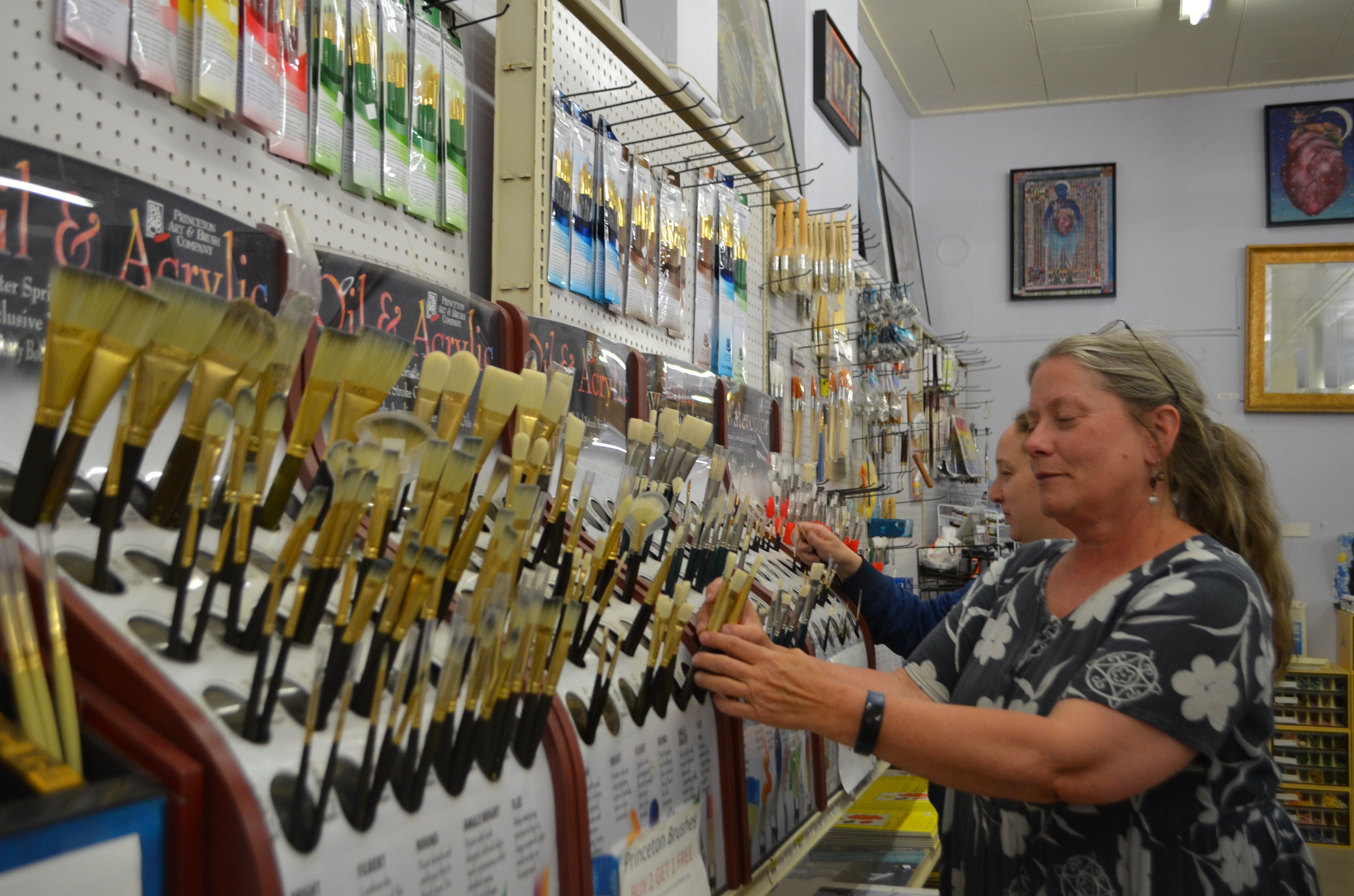 Diana Ingalls Leyba and an employee stock paintbrushes at Leyba and Ingalls Art Supply and Gallery on Friday. (Press Staff Photo by David Marquez)
