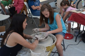 (Press Staff Photo by David Marquez)  Rosa Gonzalez instructs Talitha Lawton, 11, during the Makers on Market event Saturday. All attendees were able to visit this booth at the end of Market Street and receive a lesson in using a clay wheel for free.