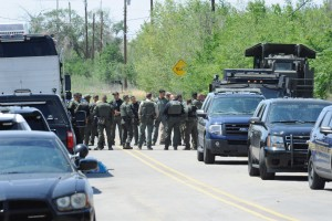 (Press Staff Photo by Geoffrey Plant)  Police gathered on North Hurley Road just before noon Friday, following the end of a standoff that left one man dead and a family's home in ruins.