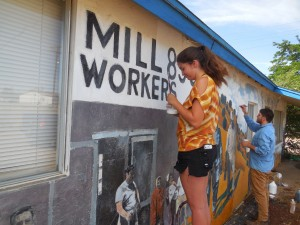 Sylvia Meyers and Javier Marrufo work to restore the Empire Zinc Mine Strike mural, located on Union Building 890 in Bayard, which was originally done over a decade ago by lead artist Fred Barraza, Diana Ingalls Leyba and students from Cobre High School. (Courtesy Photo)
