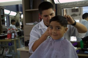 (Press Staff Photo by C.P. Thompson)  Cruz Sanchez gives a haircut to Dominic Arredondo, 6, Saturday at The Silver Clipper Barber Shop. Arredondo is going to be a first-grader at G.W. Stout Elementary School.