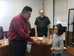 Mayor Pro Tem Raul Villanueva shakes hands with Alexis Carrillo during a Bayard City Council meeting Monday. The council approved a proclamation recognizing and honoring the Copper Little League Minor Girls team. (Press Staff Photo by C.P. Thompson)