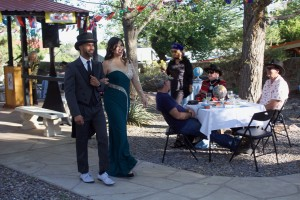 "(Press Staff Photo by C.P. Thompson)  Chris Copeland and Monique Reyes walk the fashion show runway during the fifth annual Hats in the Garden on Sunday at Western New Mexico University. The event was hosted by the WNMU Foundation, and this year's theme was ""Around the World."""