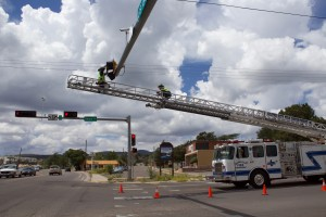 Silver City firefighters change out the red stoplight on Swan Street and U.S. 180 Tuesday. Acting Capt. Paul Ortiz said lights are changed a couple to several times a month. (Press Staff Photo by C.P. Thompson)