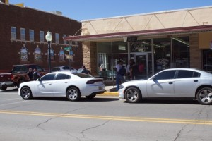 Two unmarked police cars park on Bullard Street in front of Allen's Silver City Jewelers, while officers stand in front of the store.
