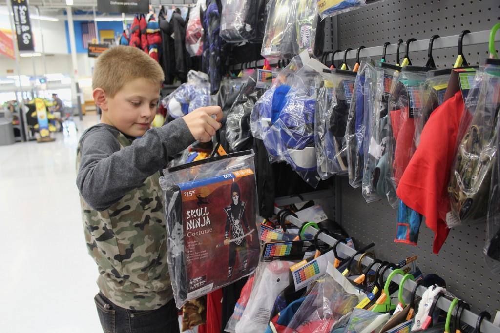 Alex Misquez checks out a costume at Walmart on Thursday. Halloween is next Thursday, Oct. 31.