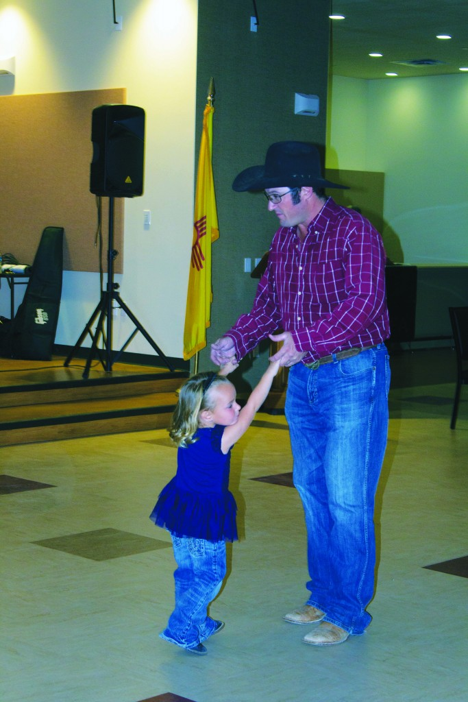 Monte and Kaydyn Topmiller dance at the Grant County Veterans Memorial Business and Conference Center on Saturday. The family dance, hosted by the Copper CowBelles, was a fundraiser for the Copper CowBelles Scholarship, said Copper CowBelles President Anette George. The scholarship is for students who would like to go into agriculture or other related fields. George would not disclose the amount of money raised from the event. (Press Staff Photo by C.P. Thompson)
