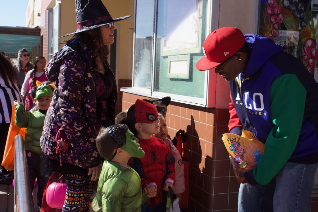 Leroy Black, with The Silver Clipper Barber Shop, hands candy to Spider-Man, Miguel Gonzalez, and the Hulk, Osias Vaughan, on Halloween on Thursday. The two superheroes, along with El Grito Head Start students, visited downtown businesses to get candy.