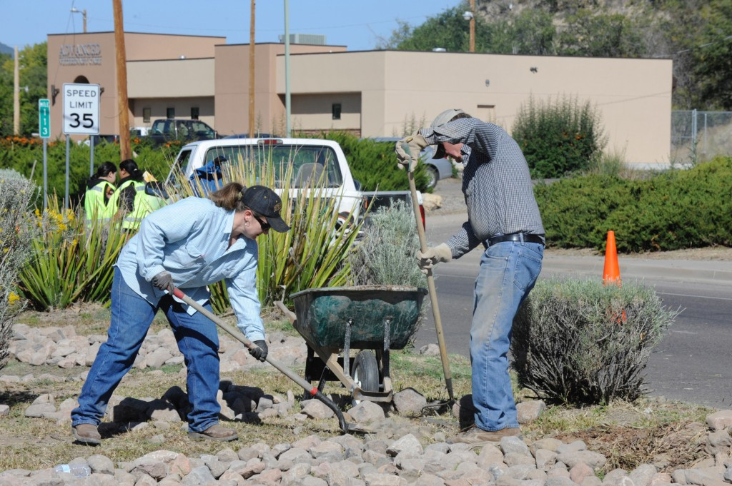 Alena Johnson and Silver City Mayor Ken Ladner install rocks for erosion control on a water catchment basin in the landscaped median on U.S. 180 between Little Walnut Road and Pope Street during the mayor's second designated volunteer day this year. About 20 youths and adults showed up for the event which was led by the mayor, Saturday morning.