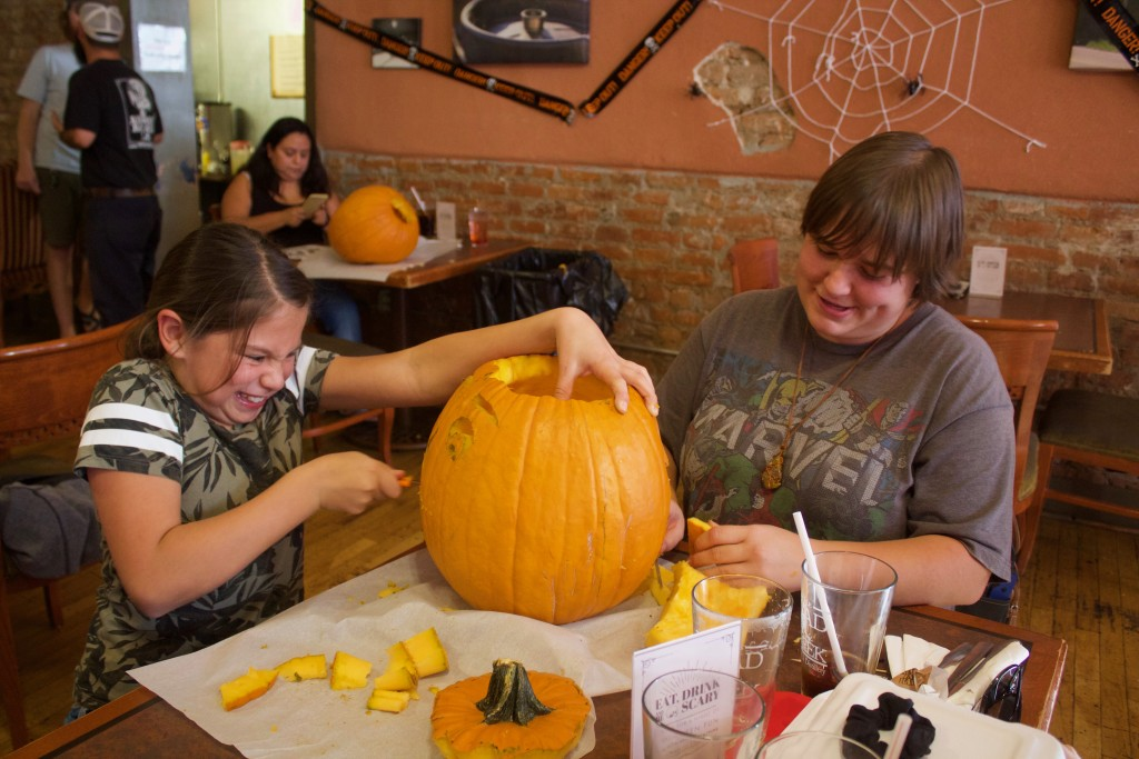 Amy Bencomo and Chelsea Boone carve a pumpkin at Little Toad Creek Brewery and Distillery on Tuesday. Kids and adults who attended the event had the chance to carve their own creations into pumpkins. Jed Bootzin, with Little Toad Creek, said this is the second year hosting the event.