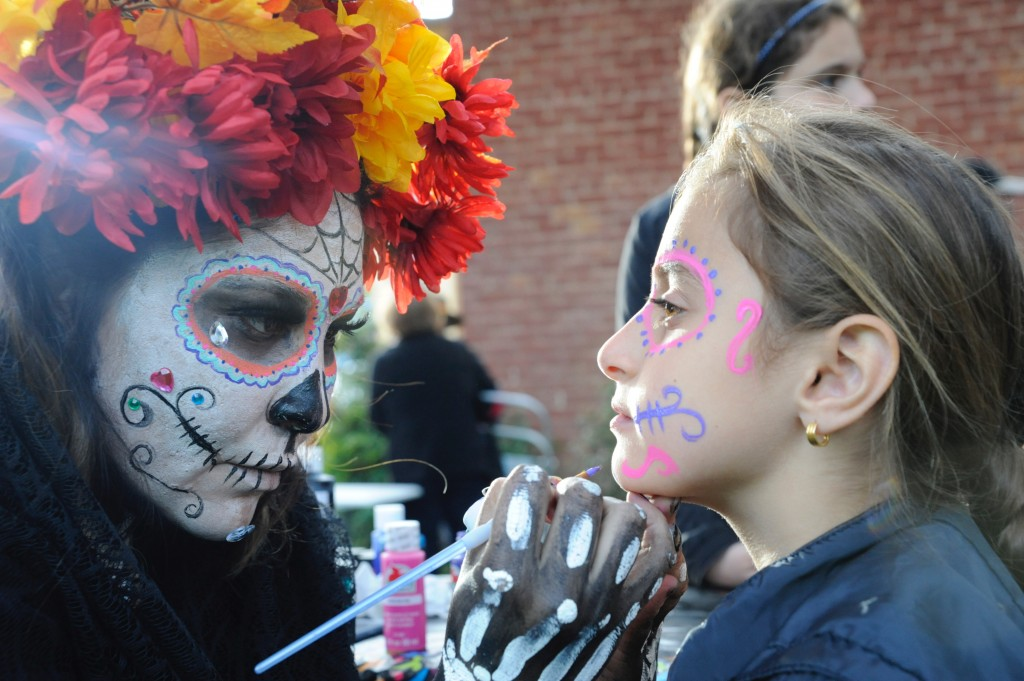 (Press Staff Photo by Geoffrey Plant)  Veronica Jimenez paints a calavera on the face of 8-year-old Daniella Batti during the Silver City Museum's Dia de los Muertos, celebration Saturday.