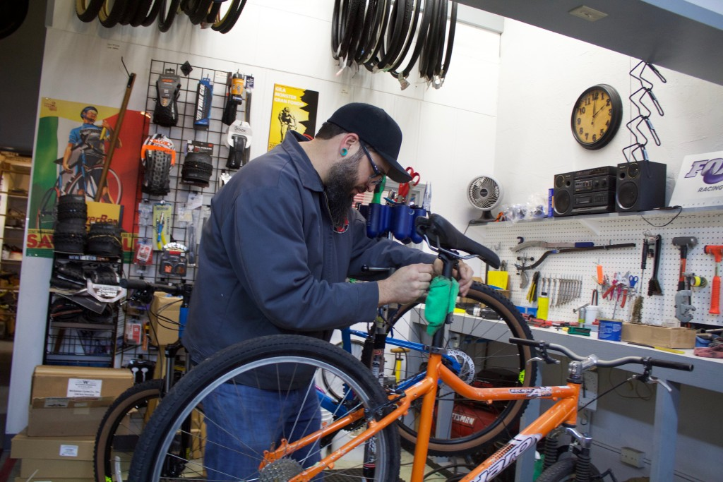A.J. Tow works on a bike at Twin Sisters Cycling and Fitness on Friday. Tow, owner of Twin Sisters, has helped fix bikes for the Gospel Mission and others. There are other Grant County local, independent businesses that have helped out the community in different ways.  (Press Staff Photo by C.P. Thompson)