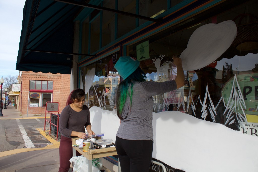 Annabella Gomez and Elysha Montoya paint an alien Christmas on the windows of the Silver City Food Co-op on Saturday.