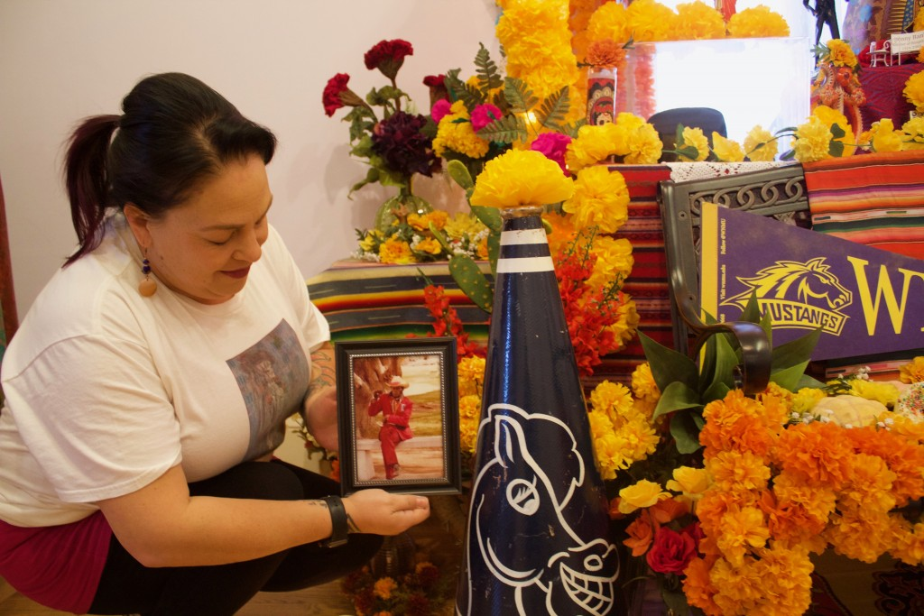 Nena Benavidez holds up a photo of Johnny Banks at the Silver City Museum on Thursday. An ofrenda was dedicated to Banks for Dia de los Muertos, and will remain up until Nov. 14. (Press Staff Photo by C.P. Thompson)