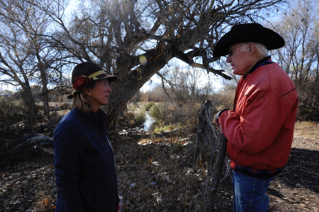 (Press Staff Photo by Geoffrey Plant)  Topper Thorpe speaks to Martha Cooper about his estimates for the flow rate in the Gila Farms Irrigation Association ditch seen behind them. Cooper manages land that abuts one of the three main pushup diversions on the Gila River, one of which feeds water into the ditch. Thorpe, a Cliff resident and a former member of the New Mexico Interstate Stream Commission, estimated that about 25 cubic feet per second was flowing into the ditch from the Gila River on Friday. Thorpe is also a member of the Fort West Irrigation Association and the former chairman of the Gila Basin Irrigation Commission, which intends to replace the three pushup dams with low-profile, fixed structures, a plan supported by Cooper — and many irrigators in the Gila Valley.