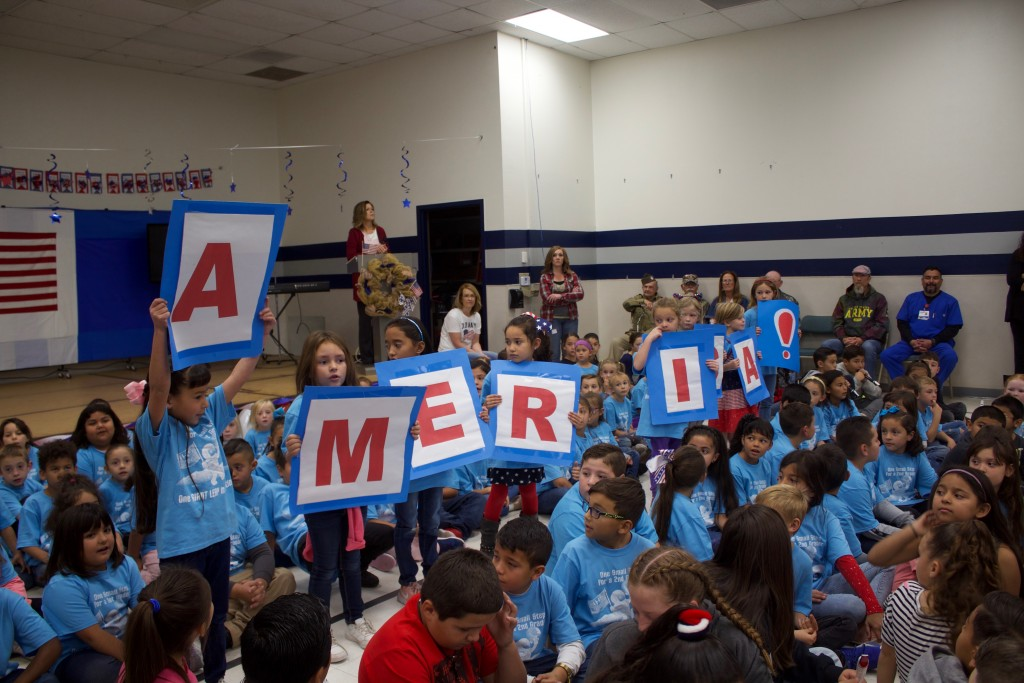 "(Press Staff Photo by C.P. Thompson) First-grader Eiley McKay Portillo holds up the letter ""A"" during a presentation at Harrison Schmitt Elementary School on Thursday. The school hosted a Veterans Day assembly, which featured World War II veteran Dan McBride as guest speaker."