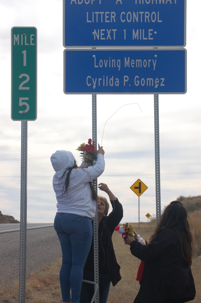 (Photo by Gwyneth Jones for the Press) Three generations, represented by Renatta Garcia, left, Terri Garcia and Martha Garcia, put up a Christmas bouquet to honor their mother, grandmother and great-grandmother, Cyrilda P. Gomez, along U.S. 180 south of Bayard on Monday. The family has adopted a mile of highway on which they conduct regular clean-ups. The extended family also includes another honoree, Avel Rios III, who died in a motorcycle crash on U.S. 180 in 2007. State highway officials recently announced planned improvements to the highway which they hope will improve safety on the heavily traveled route.