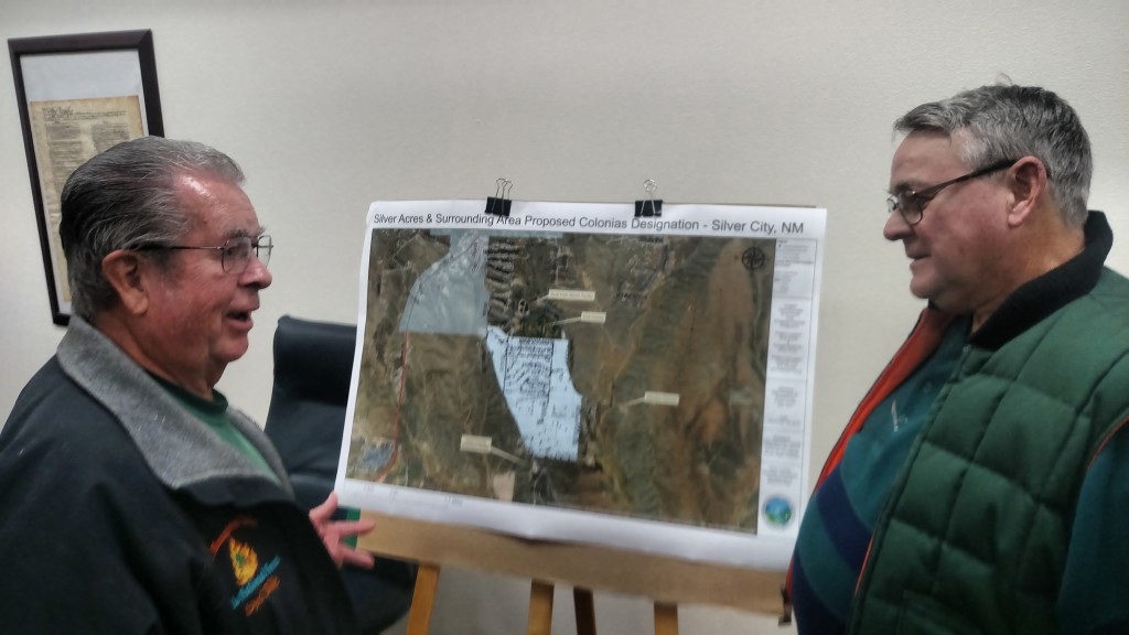 (Press Staff Photo by Kendra Milligan) Silver Acres subdivision residents and neighbors Loyd Dille, left, and Bob Yost review a map of the proposed area to be considered for Colonias designation by the Grant County Commission during a public meeting on the proposal held Thursday evening, Dec. 19, 2019.
