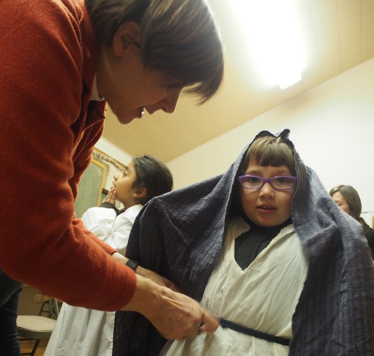 "Deacon Sarah Guck of the Episcopal Church of the Good Shepherd helps Hero Lopez dress as Mary before she and Joseph begin their pilgrimage in downtown Silver City, looking for refuge for the night. During the event, Mary, Joseph and three shepherds knocked on doors in ""Bethlehem"" to find refuge after a long pilgrimage."