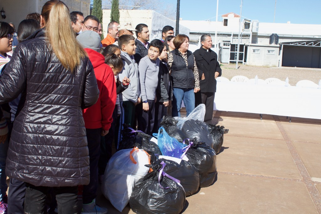 (Press Staff Photo by C.P. Thompson) People stand next to clothing in Palomas on Tuesday. Grupos Beta puts on an annual drive for clothing for migrants, where schools, churches and others donated. Grupos Beta is also working to open a refugee shelter in Palomas early next year.
