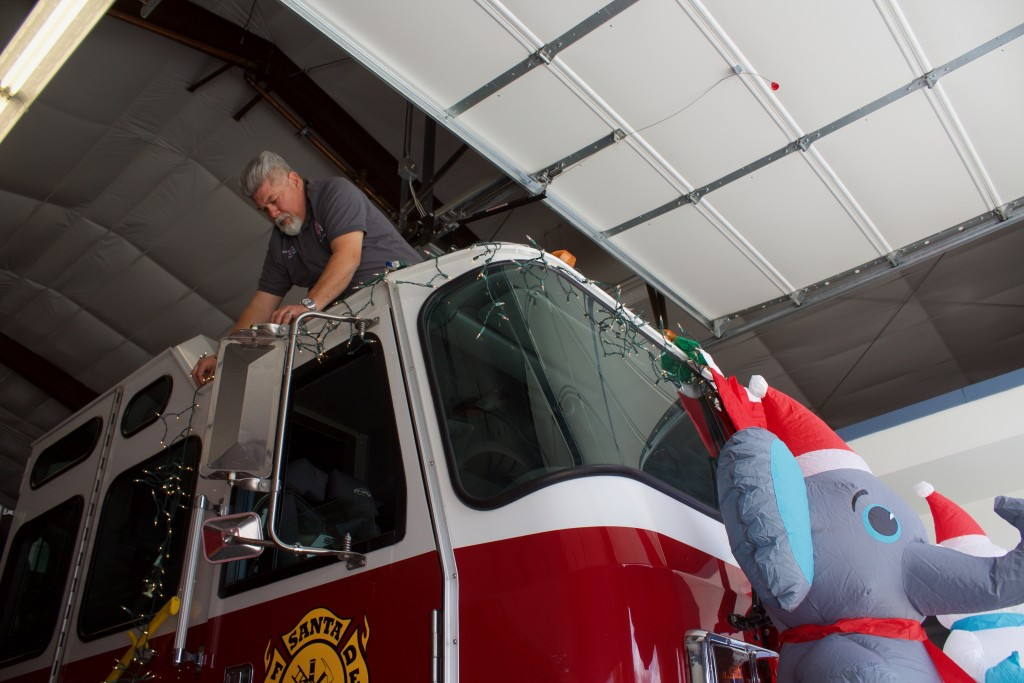 (Press Staff Photo by C.P. Thompson) Santa Clara Fire Department Fire Chief JoeAdam Gallegos puts lights on a firetruck Thursday. The sixth annual Santa Clara Lighted Holiday Parade begins around 6:30 p.m. Saturday, and anyone can enter a float before then.