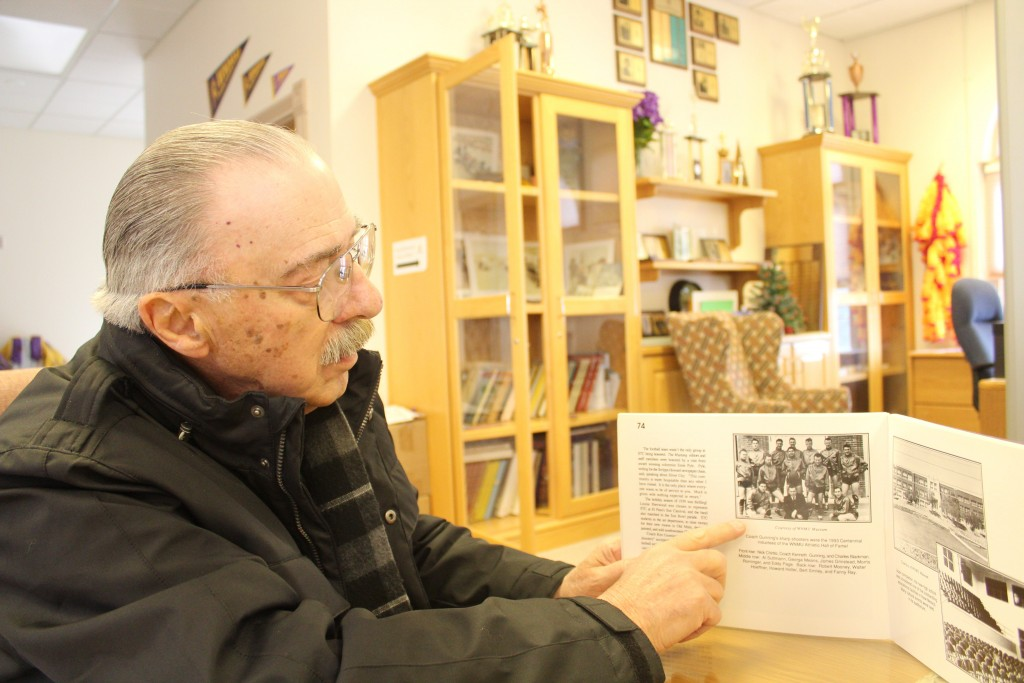 (Press Staff Photo by C.P. Thompson) Pep Parotti looks at a photo of Western New Mexico University's 1939-40 men's basketball team Friday. The team beat UCLA and Loyola University that year.