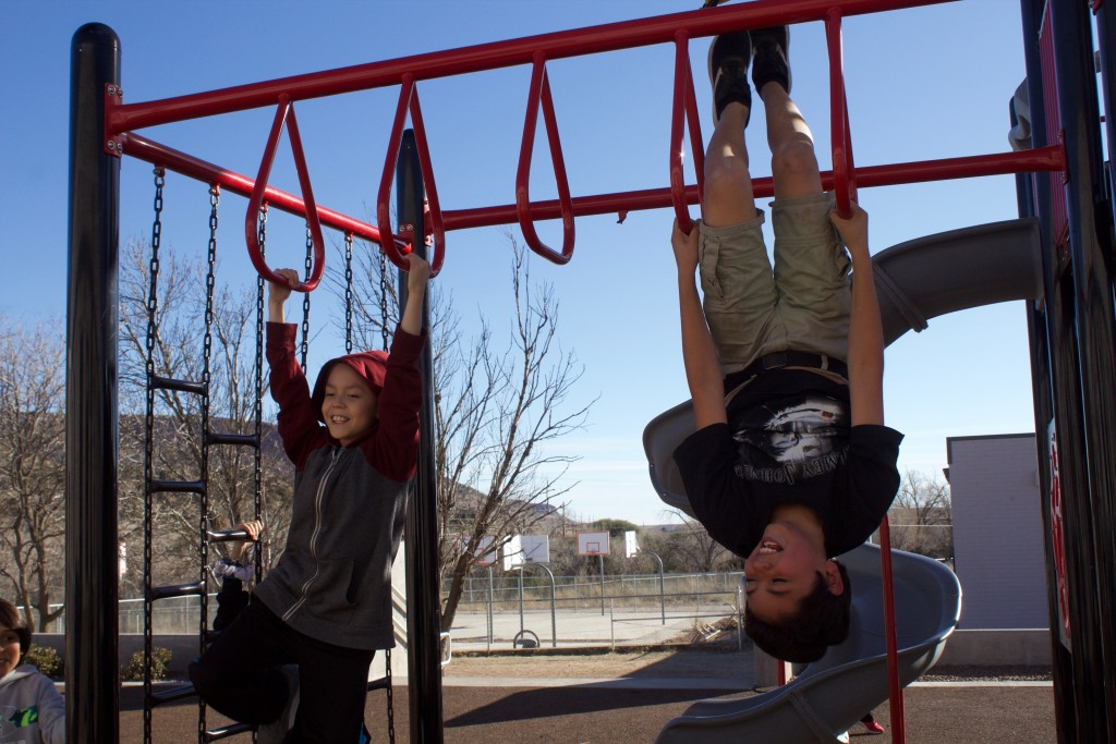 Bayard Elementary School students Michael Rivera and Jared Sifuentes fool around on a jungle gym Monday.