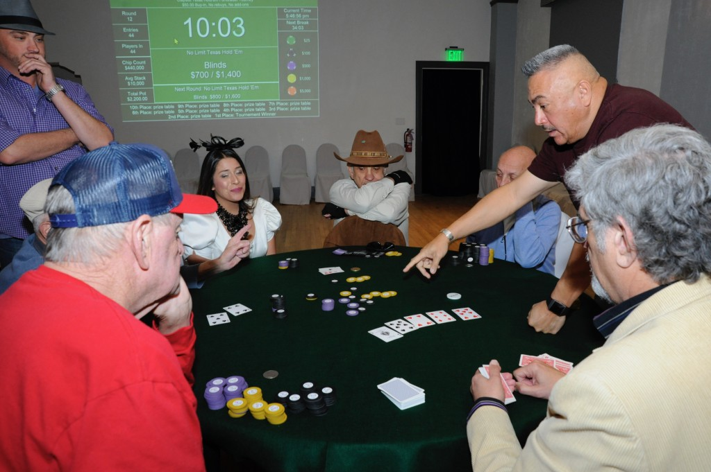 (Press Staff Photo by Geoffrey Plant)  King Crowder, host of this year's CLAY Festival Poker Tournament, looks on as Sam Rodriguez points to Melvyn Gelb's losing hand during a dramatic moment that saw Gelb (obscured by Harold Bray) knocked out of the tournament. John G. Alvarez (cowboy hat) collected an $11,000 pot — with the help of an ace in the river. Also pictured are Maria Stevens-Cook, dealer Michael Giusto and Bruce Wilson.