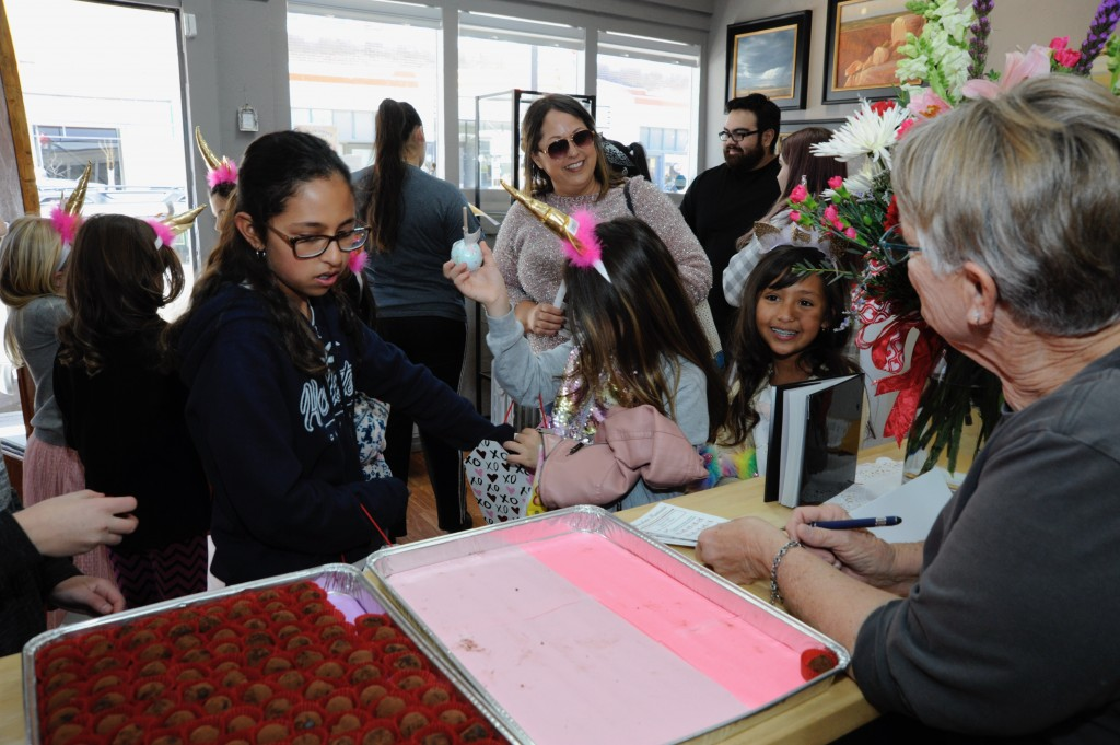 (Press Staff Photo by Geoffrey Plant)  Ava Abeyta (9, smiling, next to flowers) celebrated her upcoming birthday by leading a party of behorned friends through Chocolate Fantasia's Cupid Carnaval on Saturday. Abeyta's actual birthday is Feb. 14, St. Valentine's Day.
