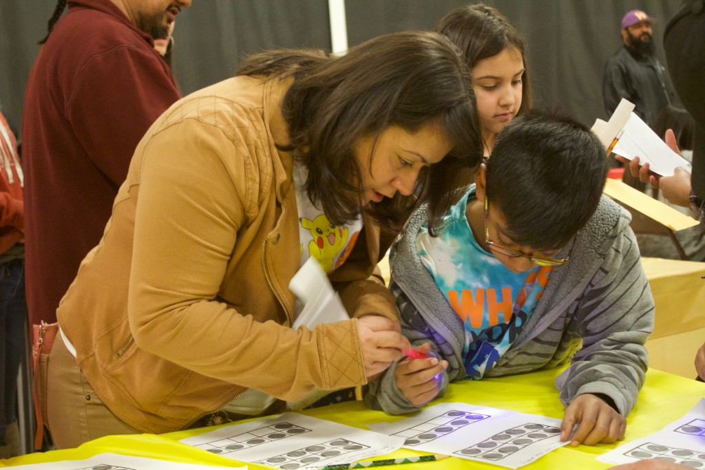 (Press Staff Photo by C.P. Thompson) Crystal and Jonah Lopez play a clue game during Family Math Learning Nights at Western New Mexico University's intramural gymnasium Wednesday. The project has been hosted at a few Grant County elementary schools, with more than 470 families attending.