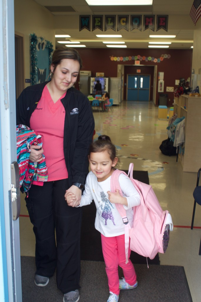 (Press Staff Photo by C.P. Thompson)  Shawni Sanchez picks up her daughter, Ilianna Placencio, from the Silver Scholars Academy pre-K on Friday. An order issued Thursday will require all school districts and charter schools to be shut down for three weeks, as of now, beginning Monday.