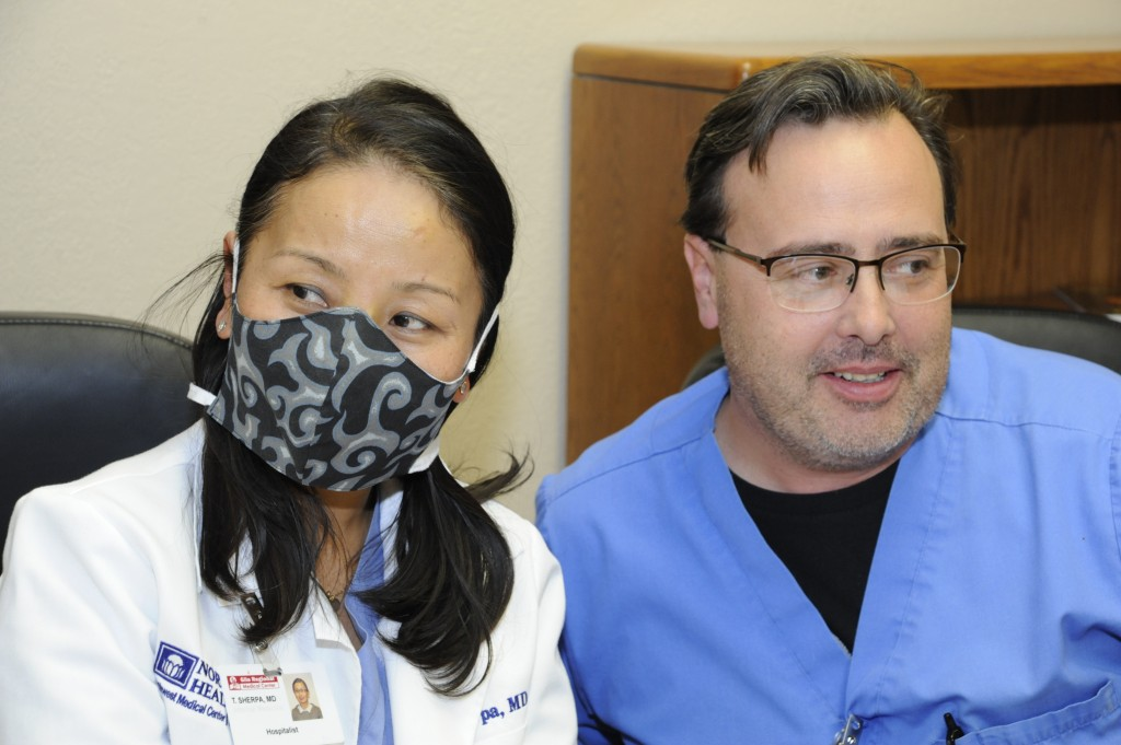 (Press Staff Photo by Geoffrey Plant)  Alongside nurse and infection specialist William Hemmer, Gila Regional Medical Center's Dr. Tsering Sherpa demonstrates a cloth surgical mask made by the hospital's auxiliary. The auxiliary has a target of 500 washable, sterilizable surgical masks that it wants to sew and supply Gila Regional with, largely for use in non-clinical areas.
