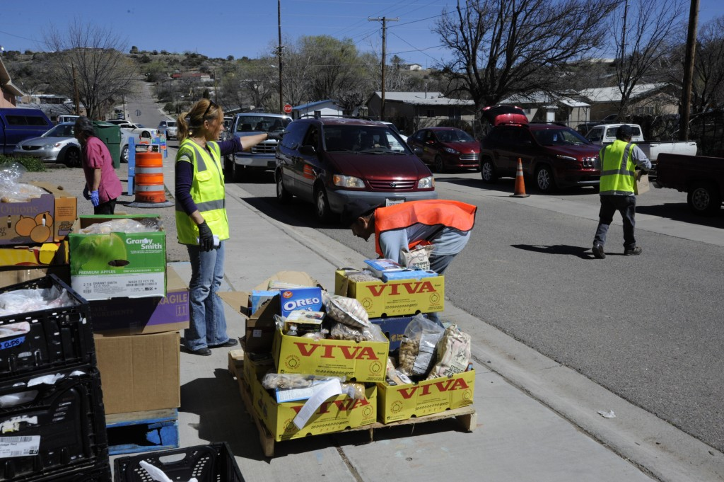 Jennifer Metzler, food pantry manager at The Commons: Center for Food Security and Sustainability, in the green vest, directs one of the volunteers who helped out during a monthly food distribution day Wednesday. (Press Staff Photo by Geoffrey Plant)
