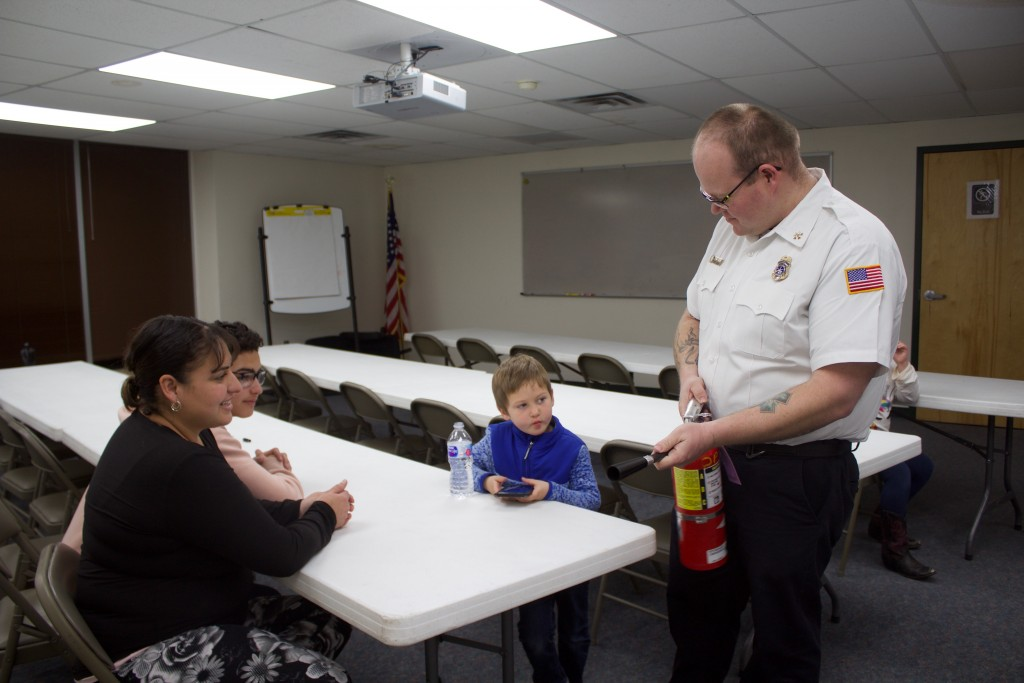 Silver City Fire Marshal Kylle Marshall shows a fire extinguisher to Marisa Marshall, Joshua Rios and Kylle Marshall Jr. at the City Hall Annex/Washington Federal building Thursday. He held a fire safety presentation and talked about carbon monovide detectors, making a home escape plan and preventing fires in a home.