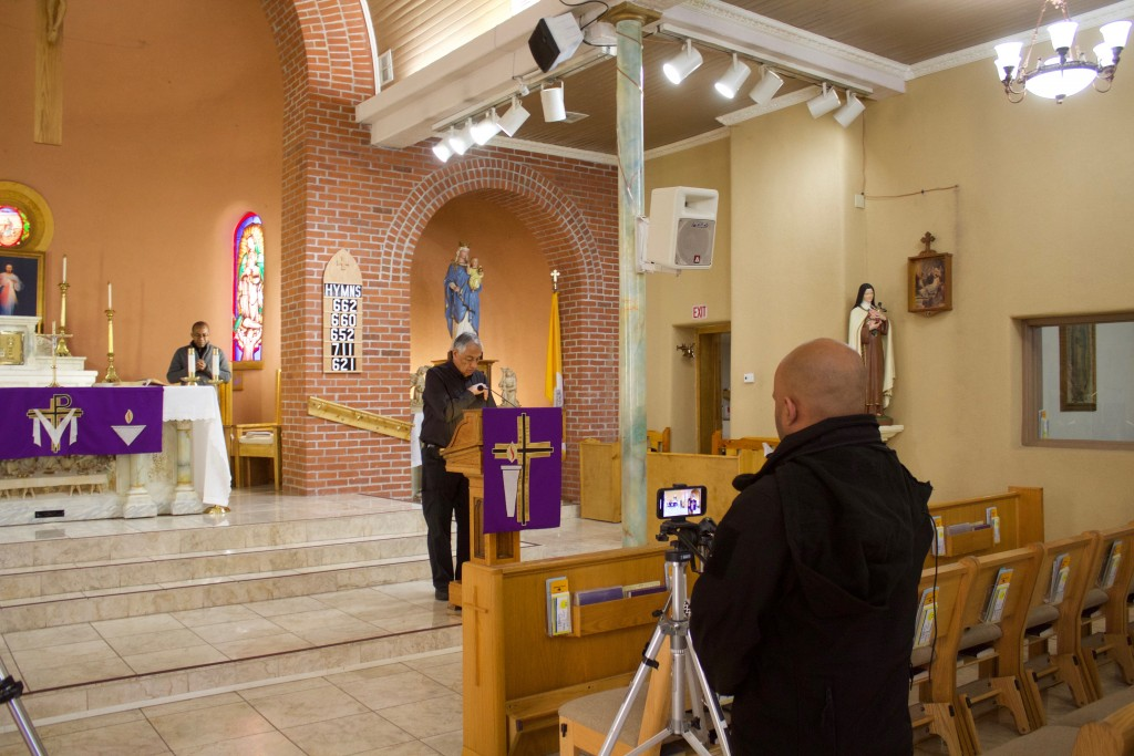 (Press Staff Photo by C.P. Thompson)  Efren Canas, Bill Holguin and Father Oliver Obele record a service at St. Vincent de Paul Roman Catholic Church on Friday. The church will stream the service on Facebook Live and it will be posted onto the church's website today.