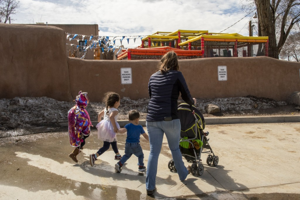 (Photo by Don J. Usner for Searchlight New Mexico) A woman walks with her children and a foster child to a play date in Taos.