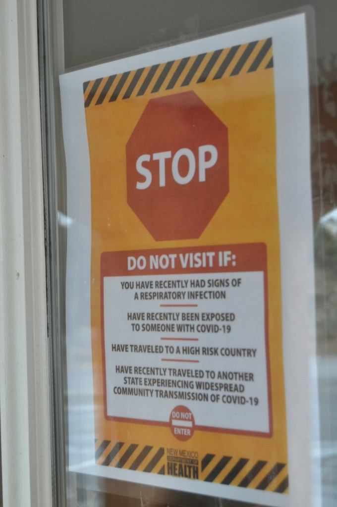 (Photo by Aaron Rogers for the Daily Press) One of several COVID-19-related warning signs posted on the door of Sunset Vista Assisted Living Facility in Silver City on Thursday.