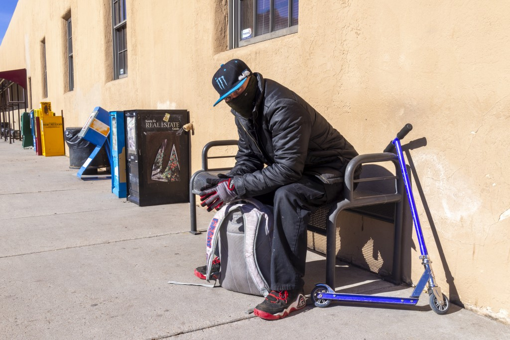 (Photo By Don J. Usner for Searchlight New Mexico) A man wearing a bandanna to protect against coronavirus waits in Santa Fe for a bus to take him to a job interview in Española.