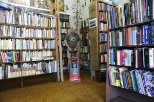 "(Press Staff Photo by Geoffrey Plant)  Dennis O'Keefe vacuums water out of his rare-book shop Sunday, after an early Saturday morning leak in a bathroom inside the historic Palace Hotel dumped hundreds of gallons of water into the space, ruining about one-fifth of O'Keefe's stock. ""At least it wasn't sewer water,"" he said. O'Keefe has been a tenant in the Palace Hotel block at Broadway and Bullard Street for 35 years."