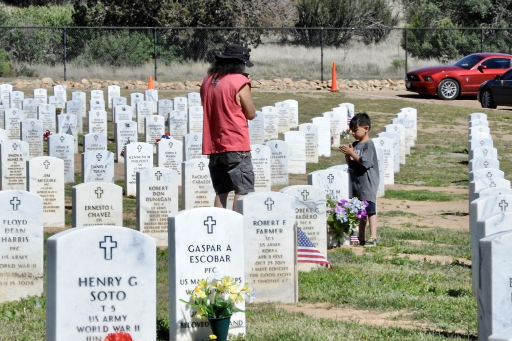"(Press Staff Photo by Geoffrey Plant) Charles V. Salas and his 5-year-old grandson, Anthony Cortez, visited multiple family graves at Fort Bayard National Cemetery on Monday, including those of Salas' mother and father, Lorenza Salas and Felix M. Salas Sr., a World War II prisoner of war and survivor of the Bataan Death March. ""It's a little off-beat or different this year,"" Salas said. ""But I understand. This pandemic has turned the community upside-down."""
